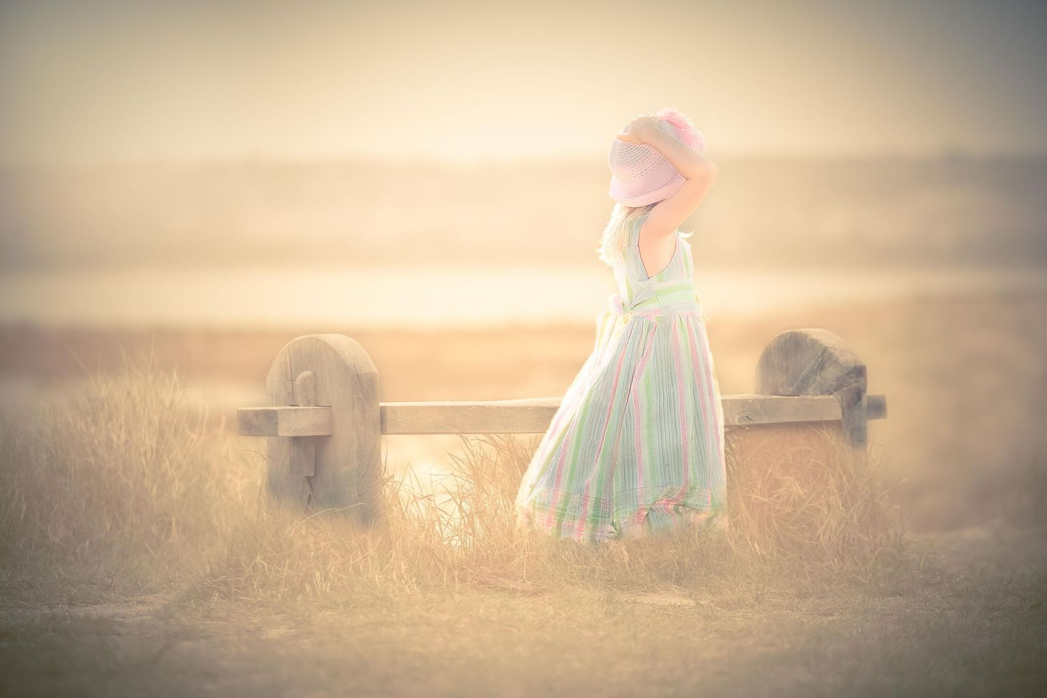 girl in a dress and hat by a bench at the beach, soft focus