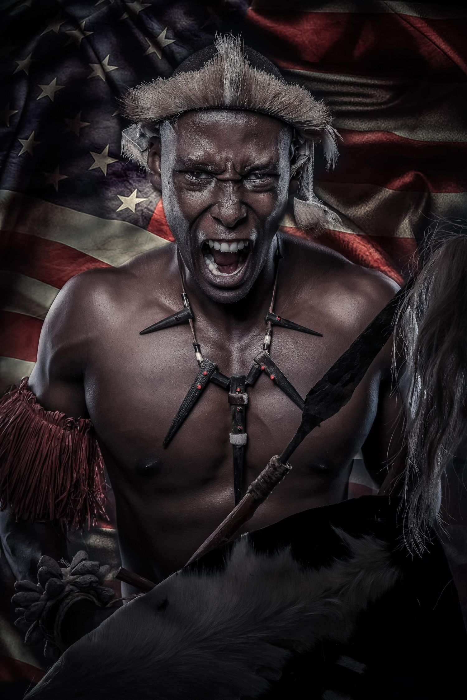 Zulu warrior screaming with American flag in background