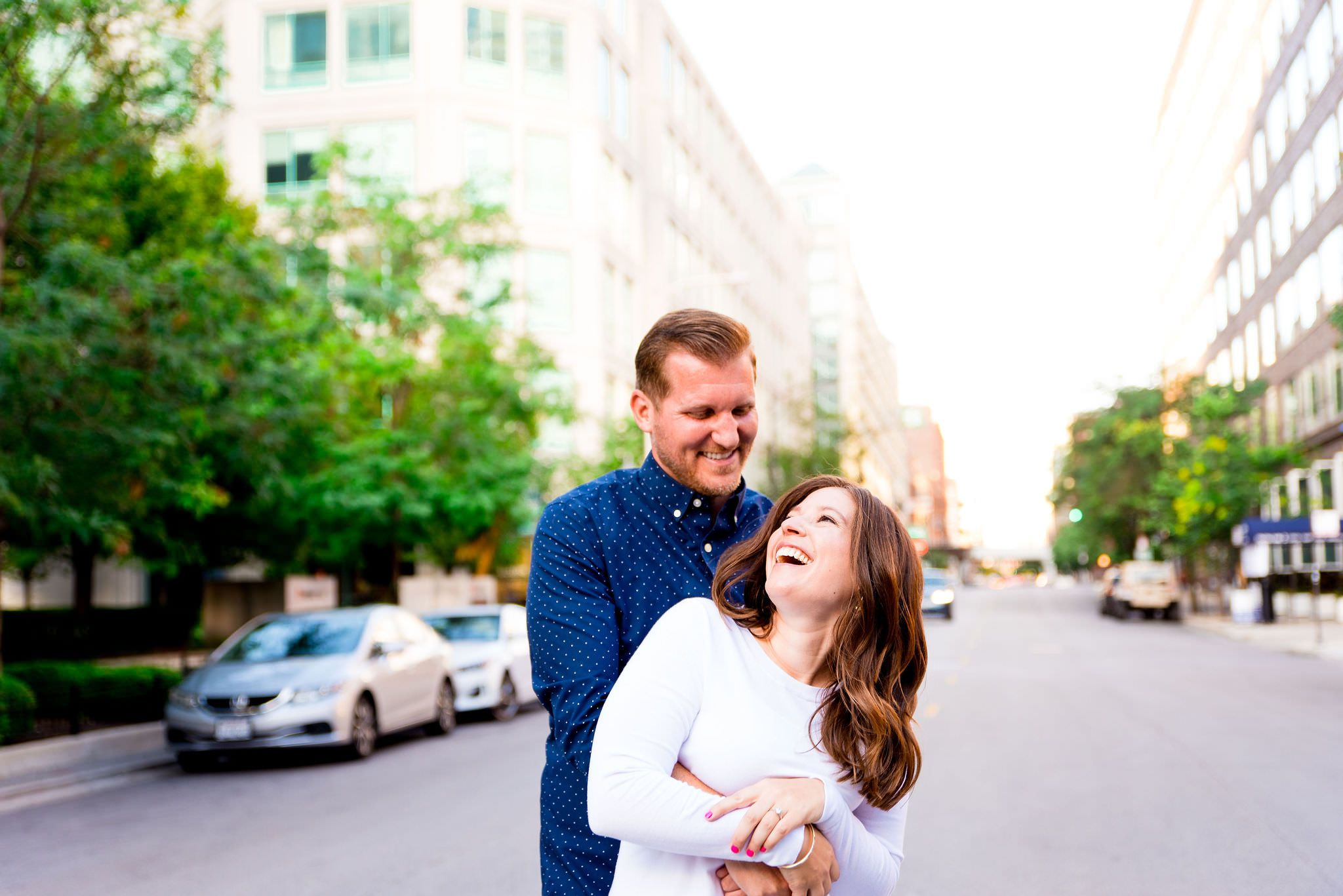 redhead man in navy shirt hugging woman in white sweater, laughing in the middle of street for sunset engagement picture