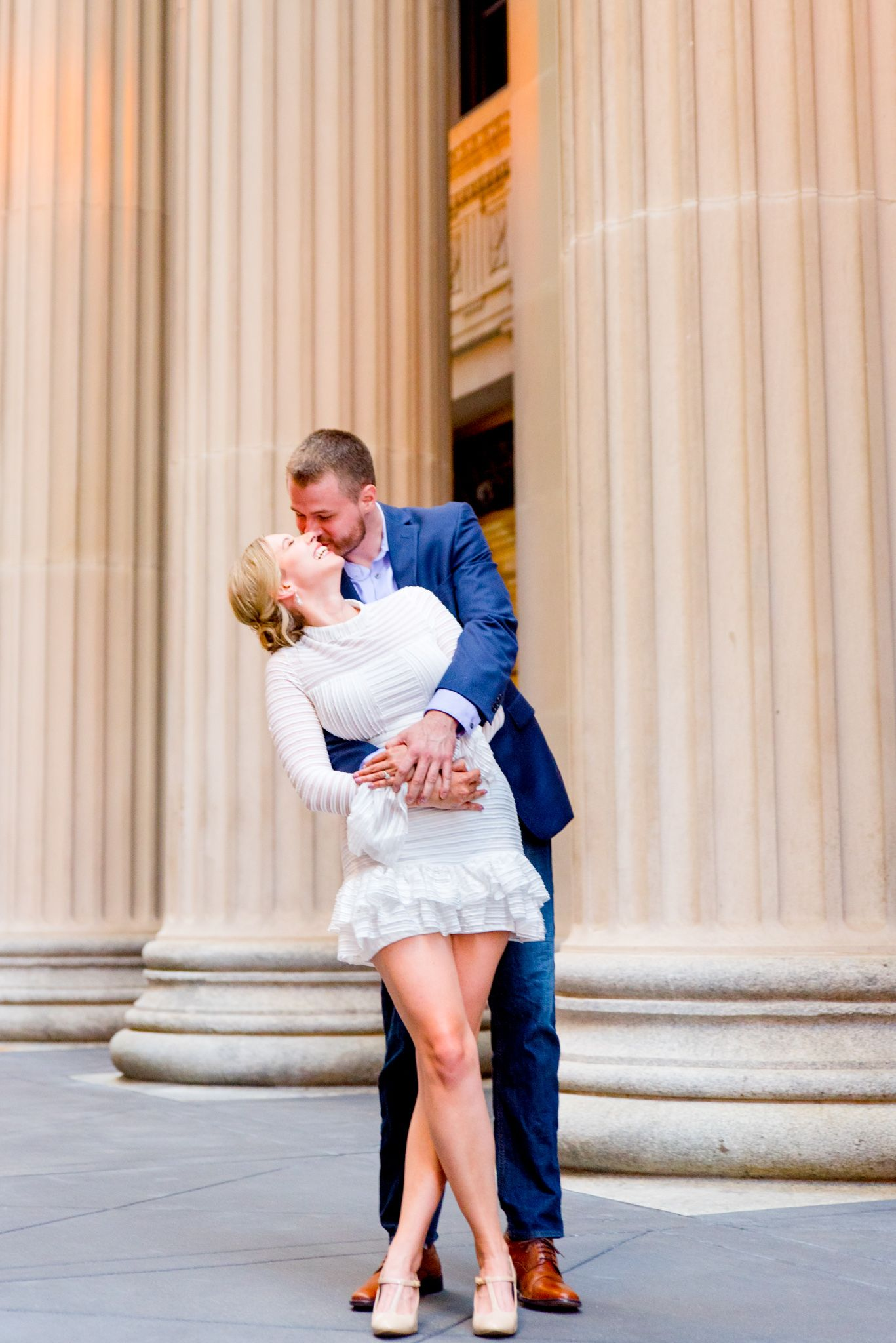 man in navy suit hugging woman in white dress from behind at Chicago Board of Trade engagement pictures