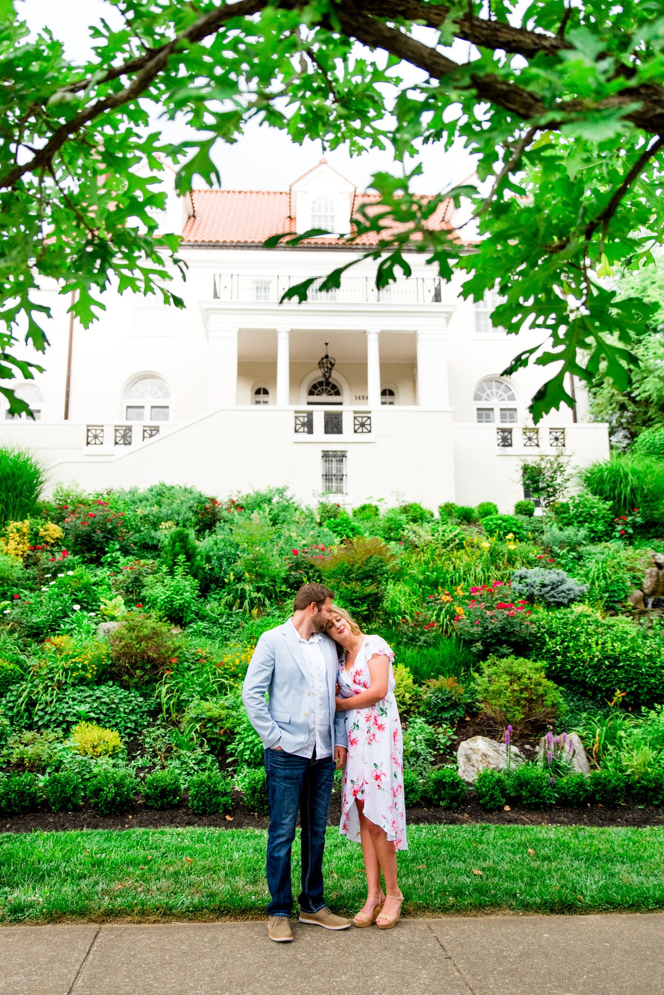 engaged couples in floral dress and light blue suit jacket and jeans standing in front of white Louisville mansion