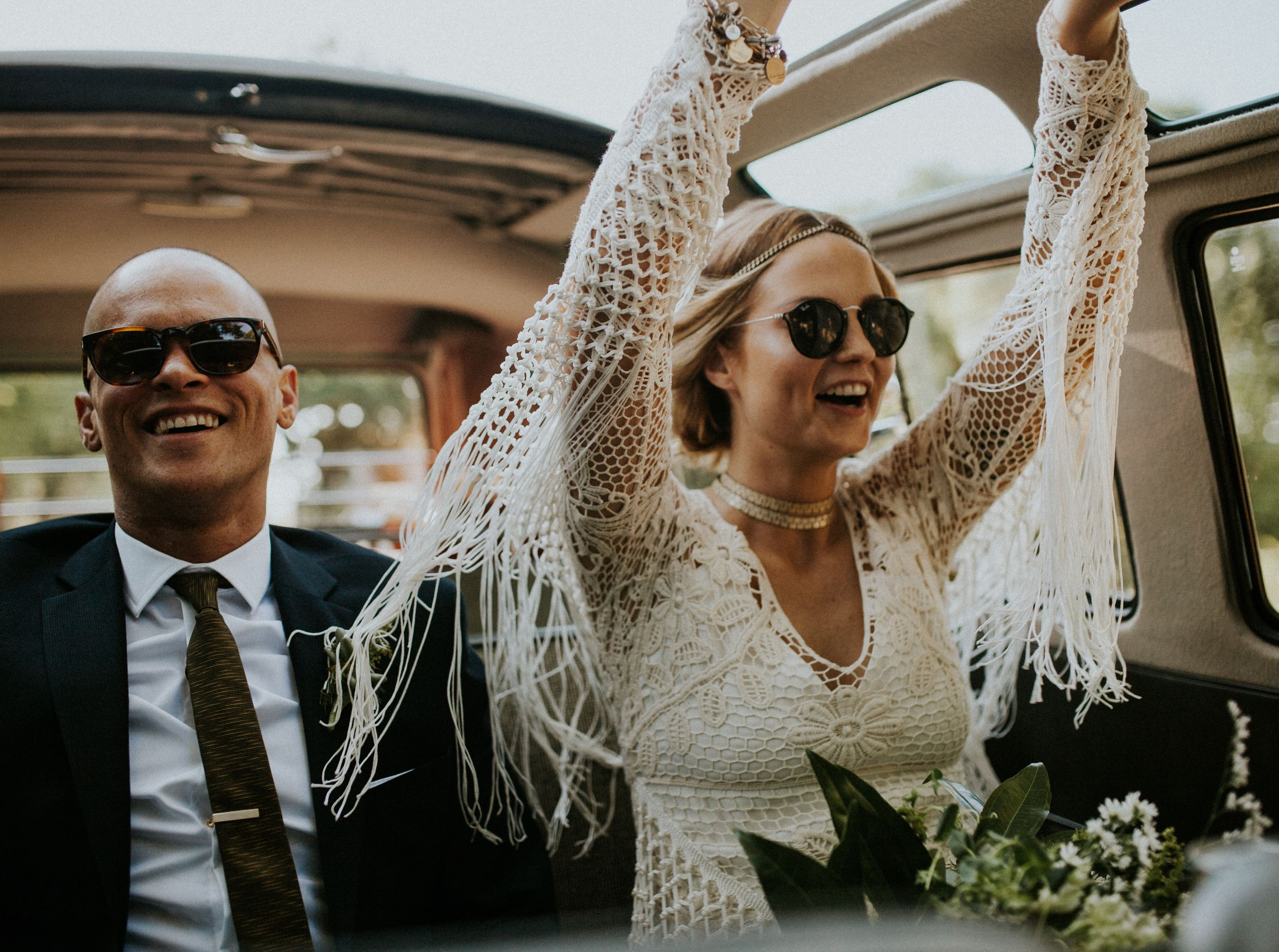 stylish bride and groom in a Volkswagen having fun with big smiles wearing sunglasses with their hands up.