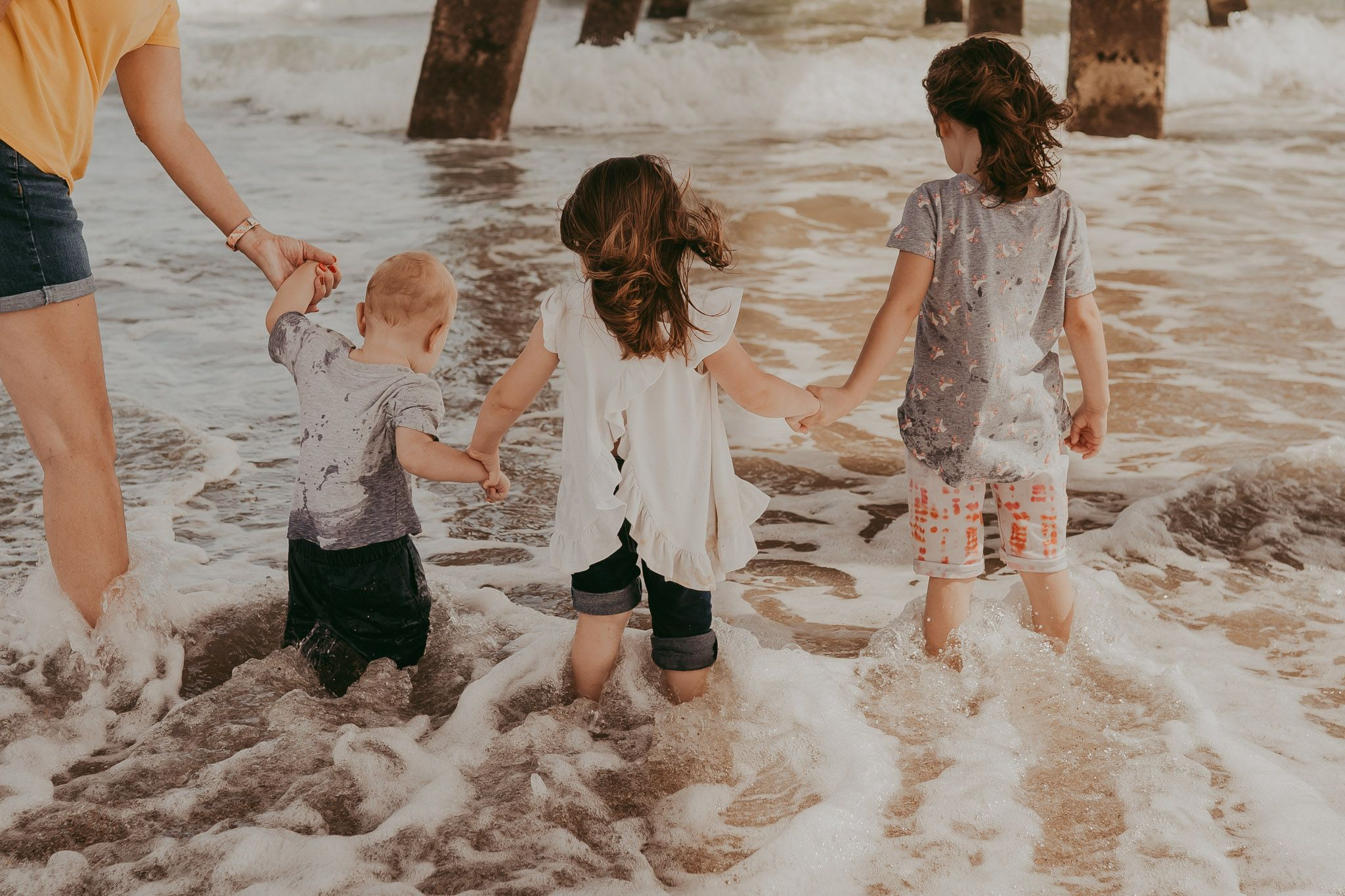Three young children are holding hands and letting the waves crash over their feet at the beach.