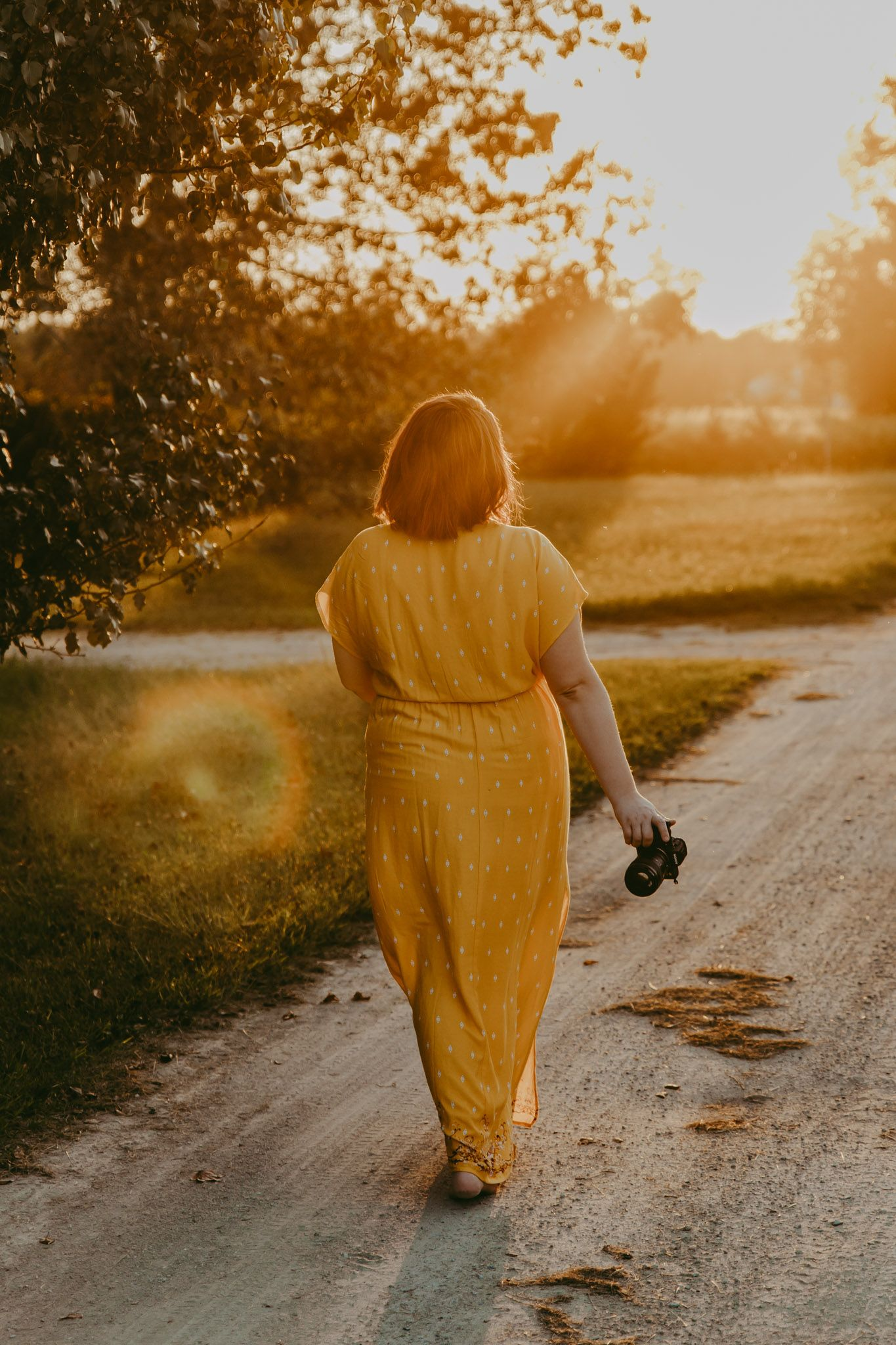 A girl is walking down a dirt path towards the setting sun with her camera in her hand.