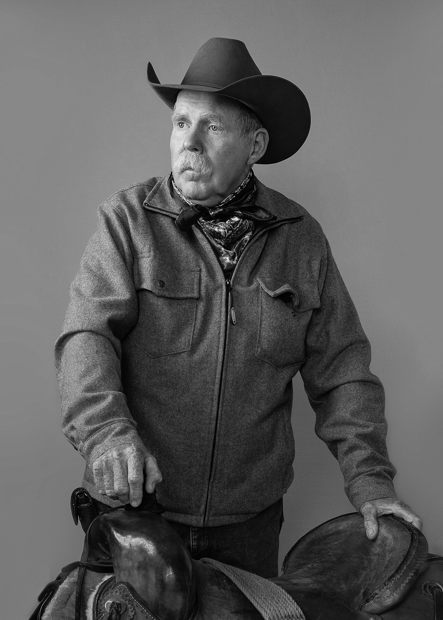 Cowboy with saddle in studio