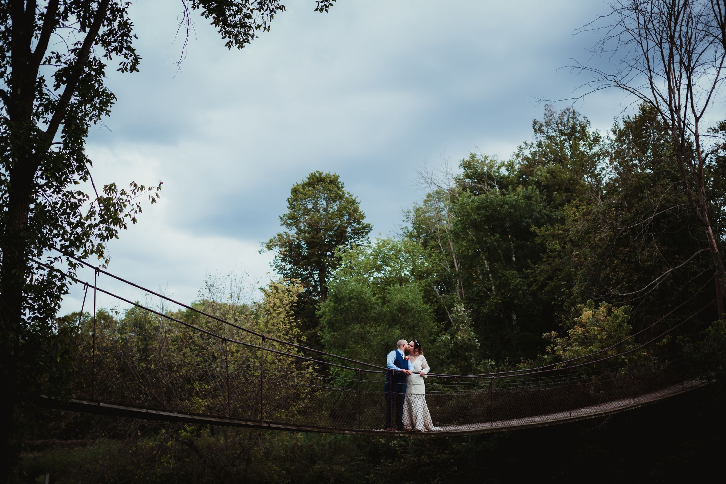 Man and woman in wedding attire kissing in the middle of a swinging cable rope bridge.