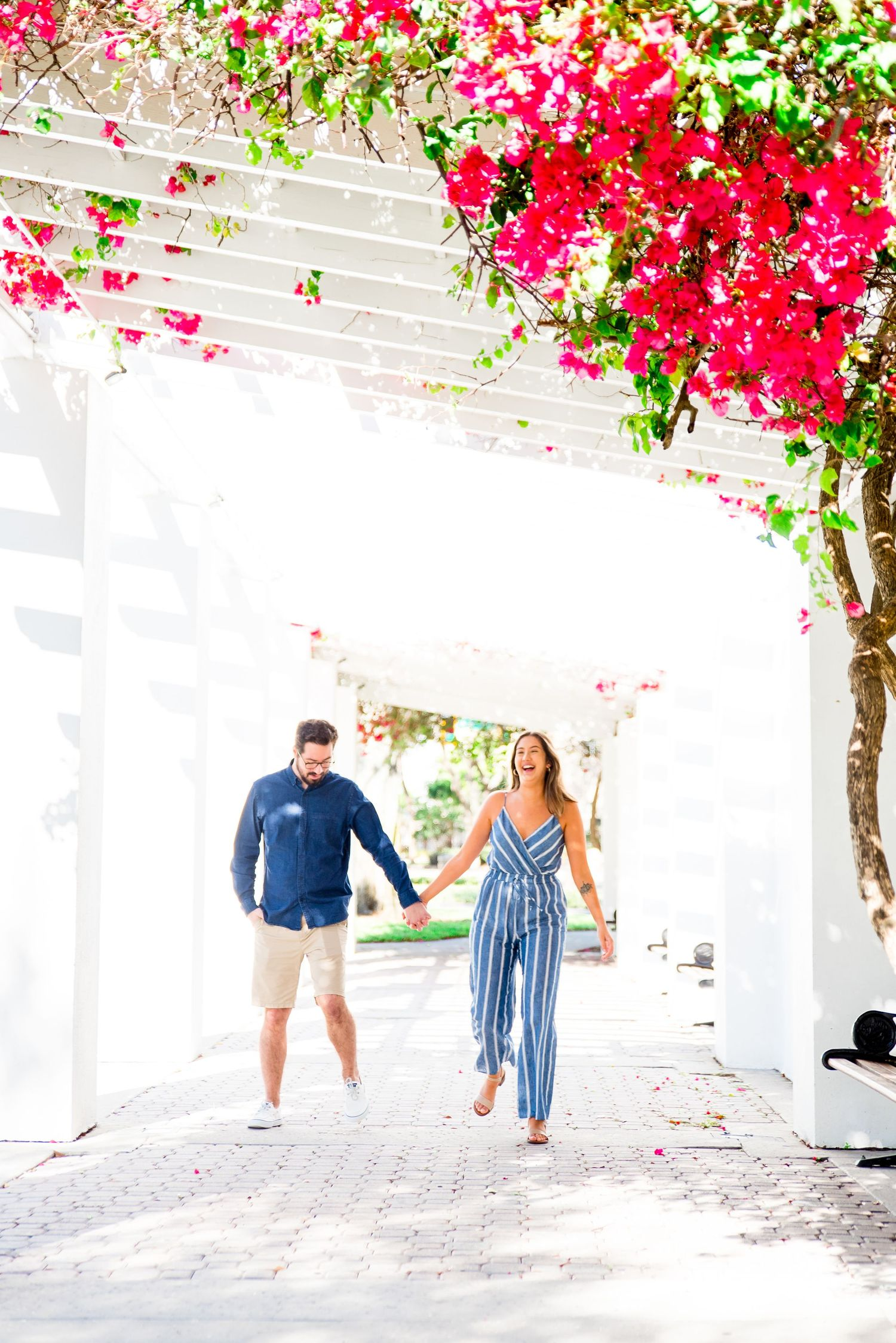 young couple in blue outfits walking and laughing at Vinoy Park St Pete engagement photos