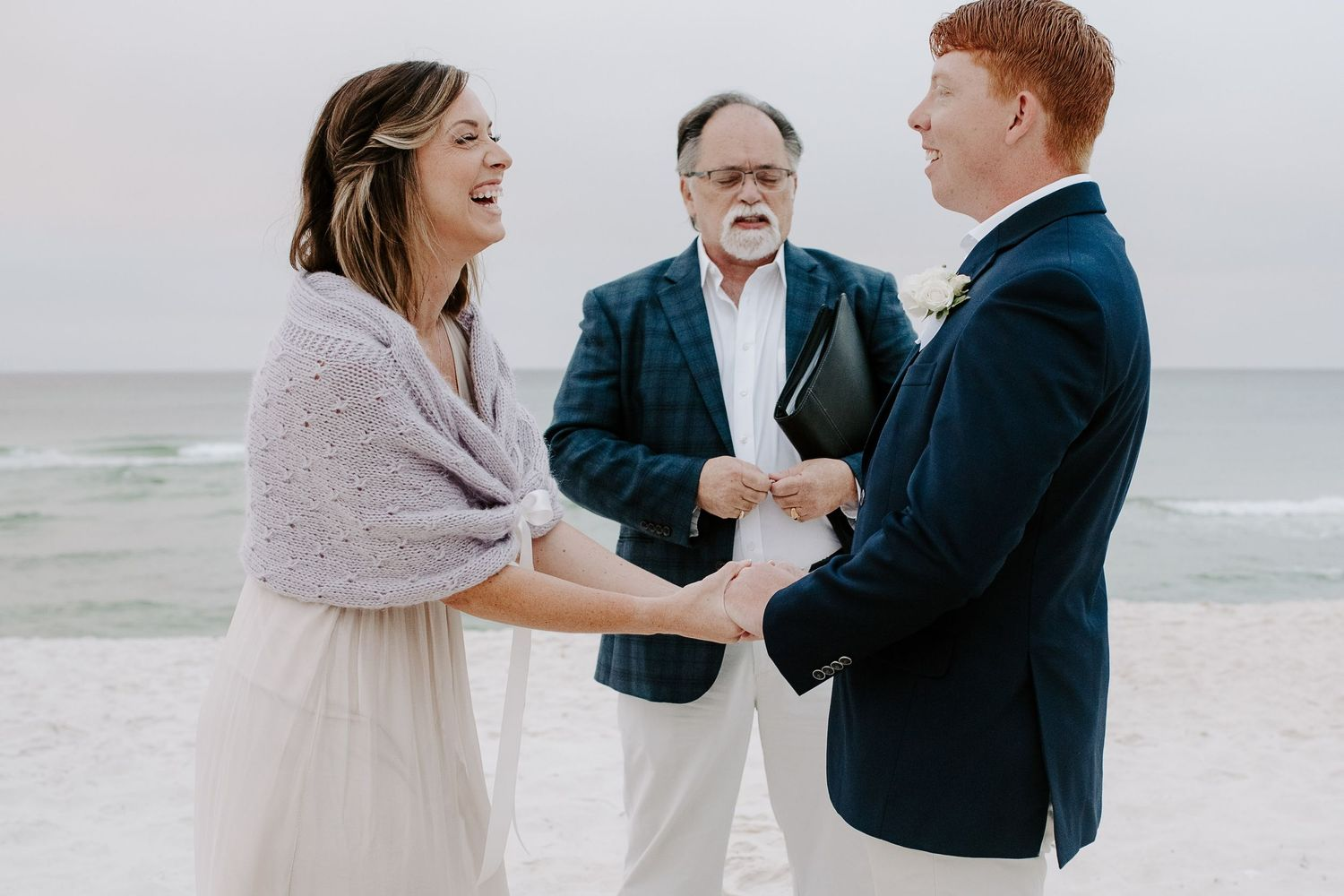 woman holding her husbands hands while saying vows during their 30A sunrise elopement