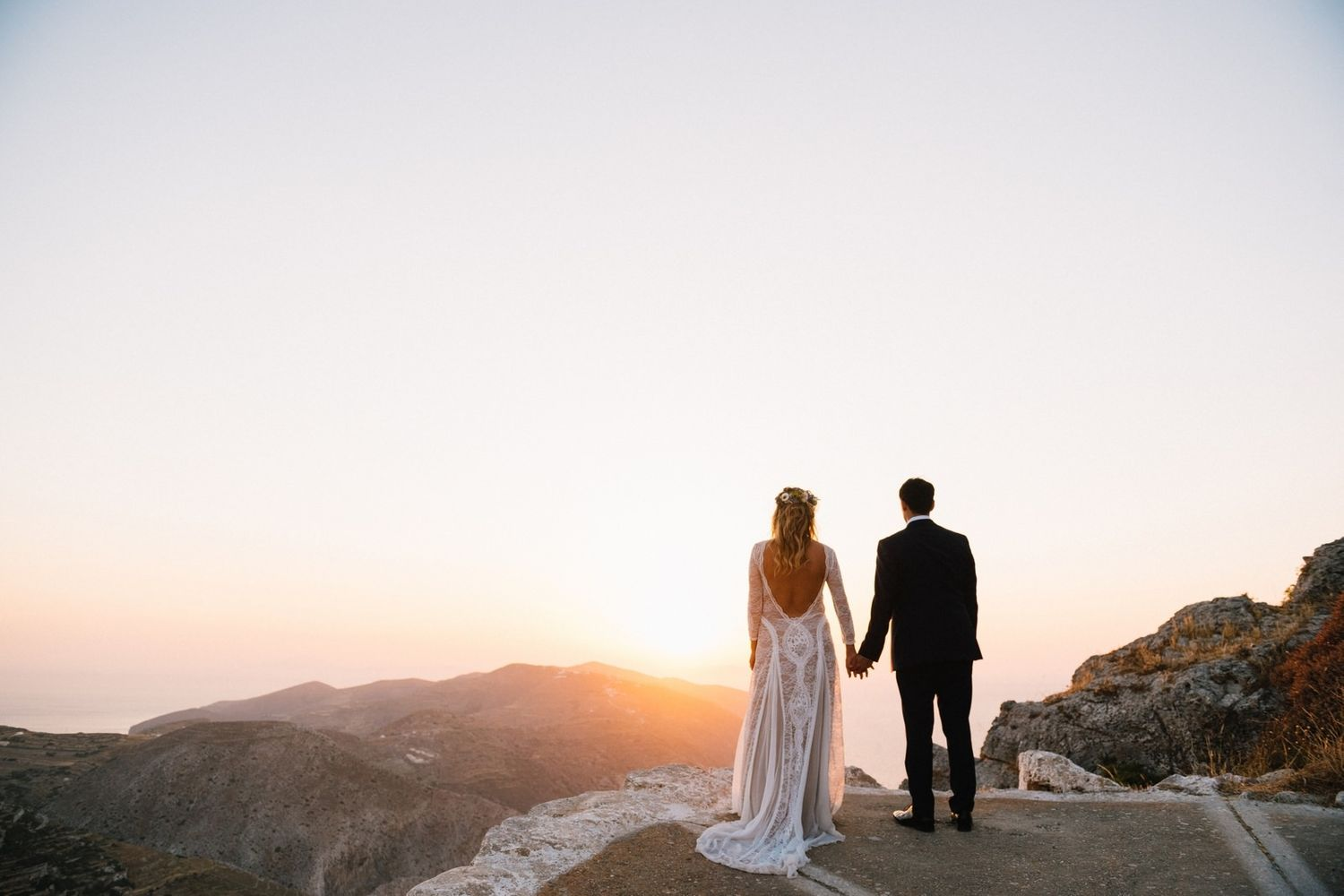 bride and groom watching the sunset at folegandros