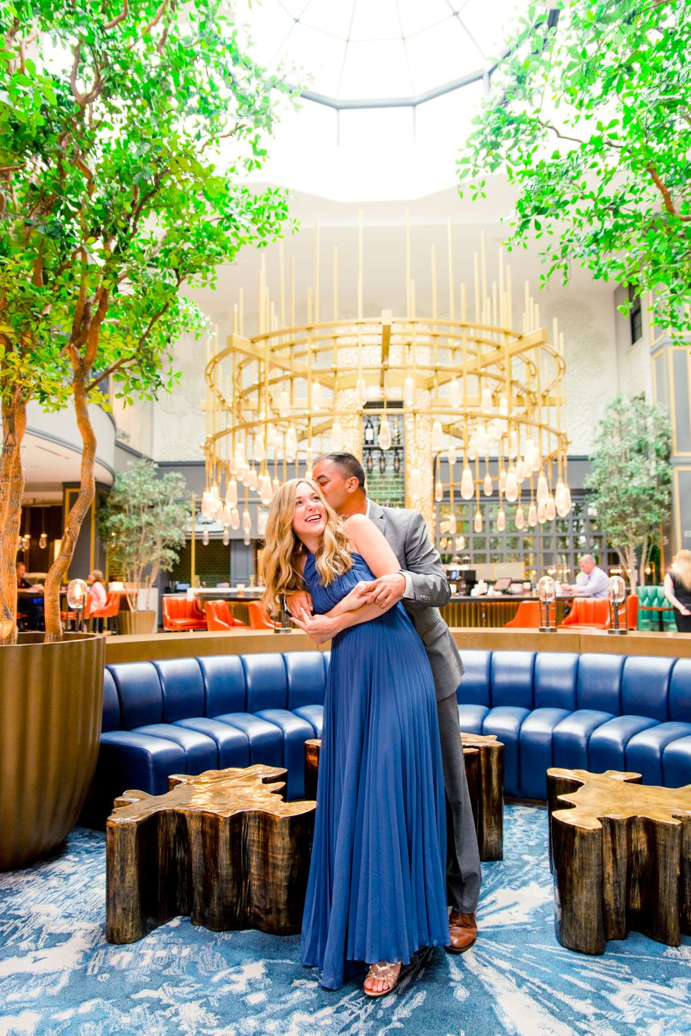 man in grey suit hugs woman in blue dress from behind in front of gold chandelier at Lytle Park Hotel bar