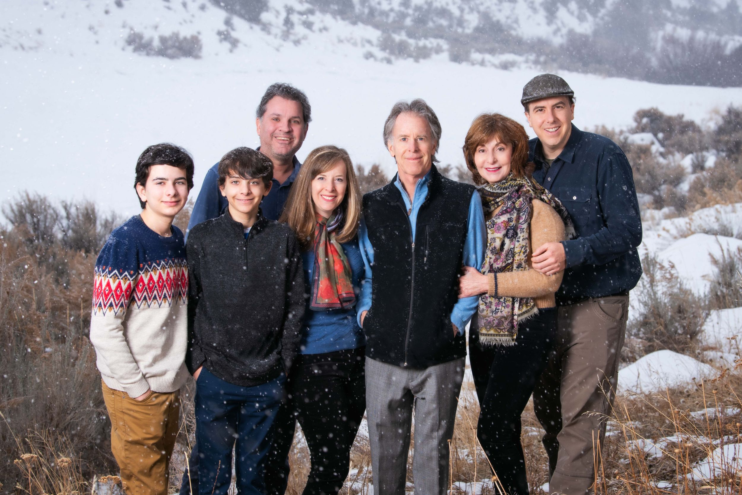 Three generations of a family outside in the mountains while it's snowing