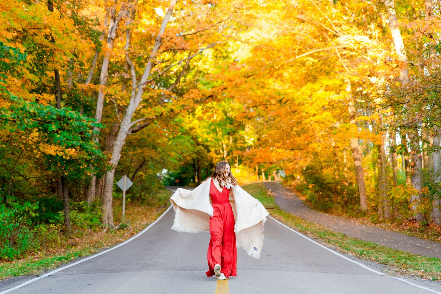 girl in orange jumpsuit dancing with a white blanket under yellow trees at Sharon Woods park in Cincinnati Ohio