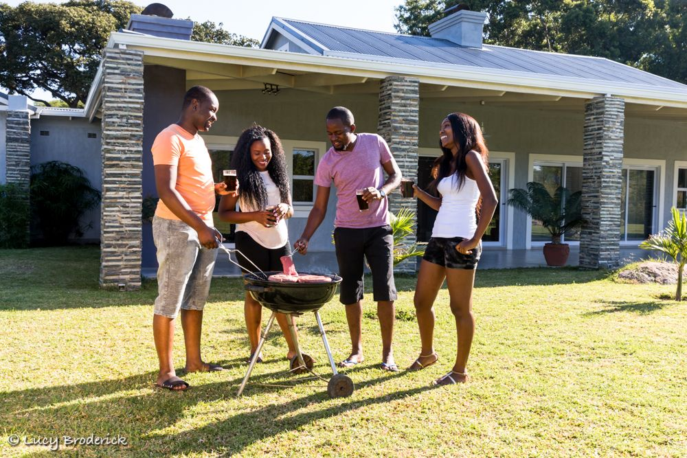 People having a braai/barbeque infront of a new house for an advert campaign