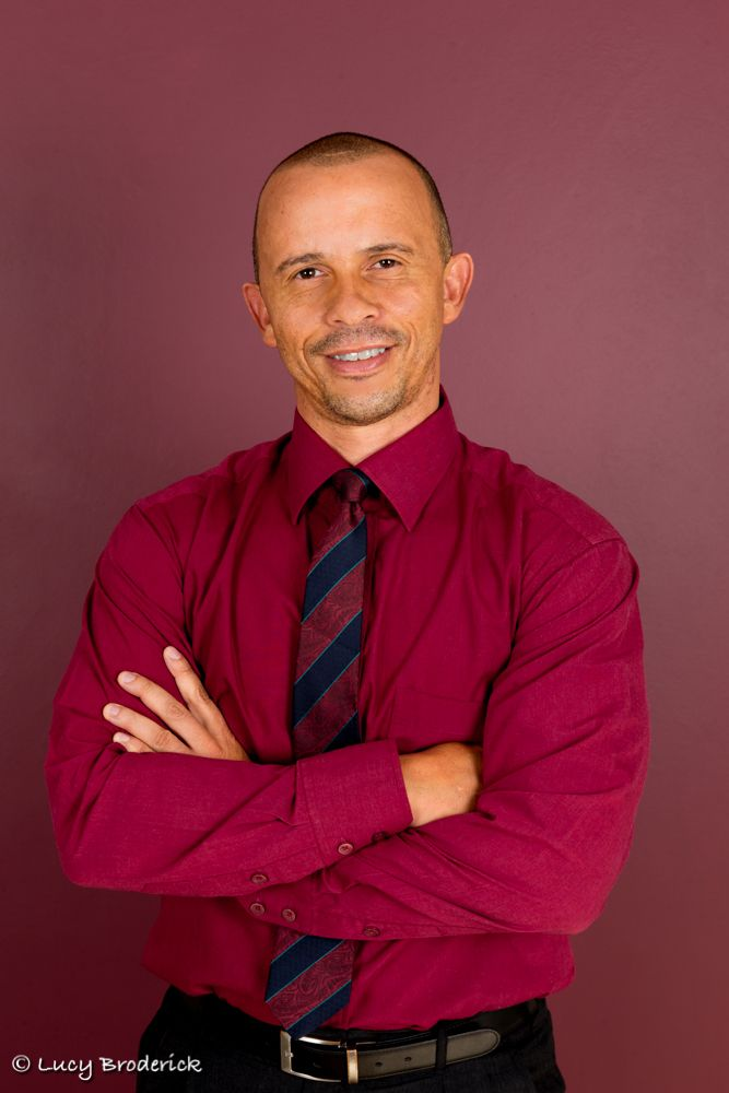 Corporate Headshot/Profile photo of a man on a red background, personal branding