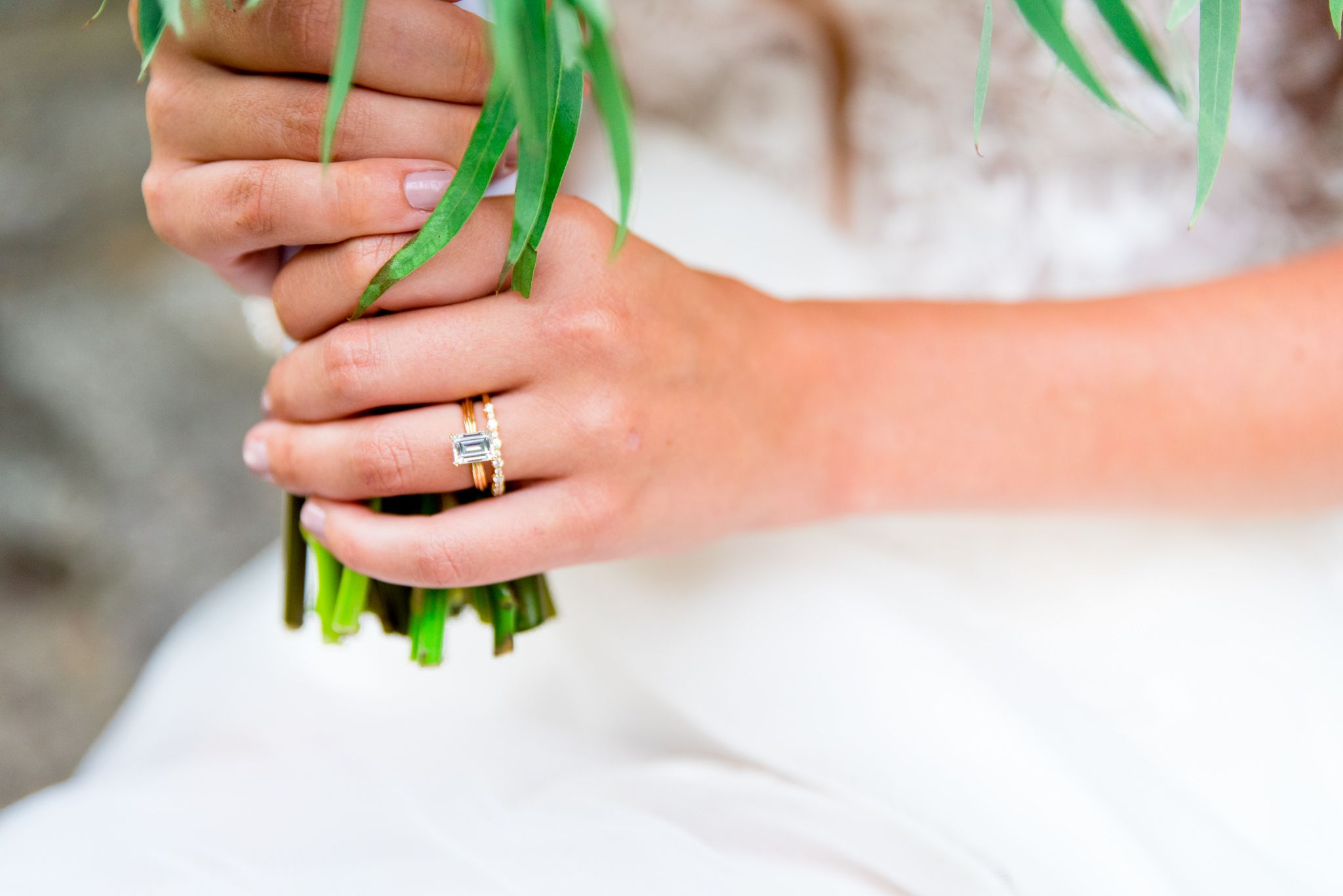 close up of hands holding a wedding bouquet with a yellow gold wedding band and emerald cut engagement ring on.