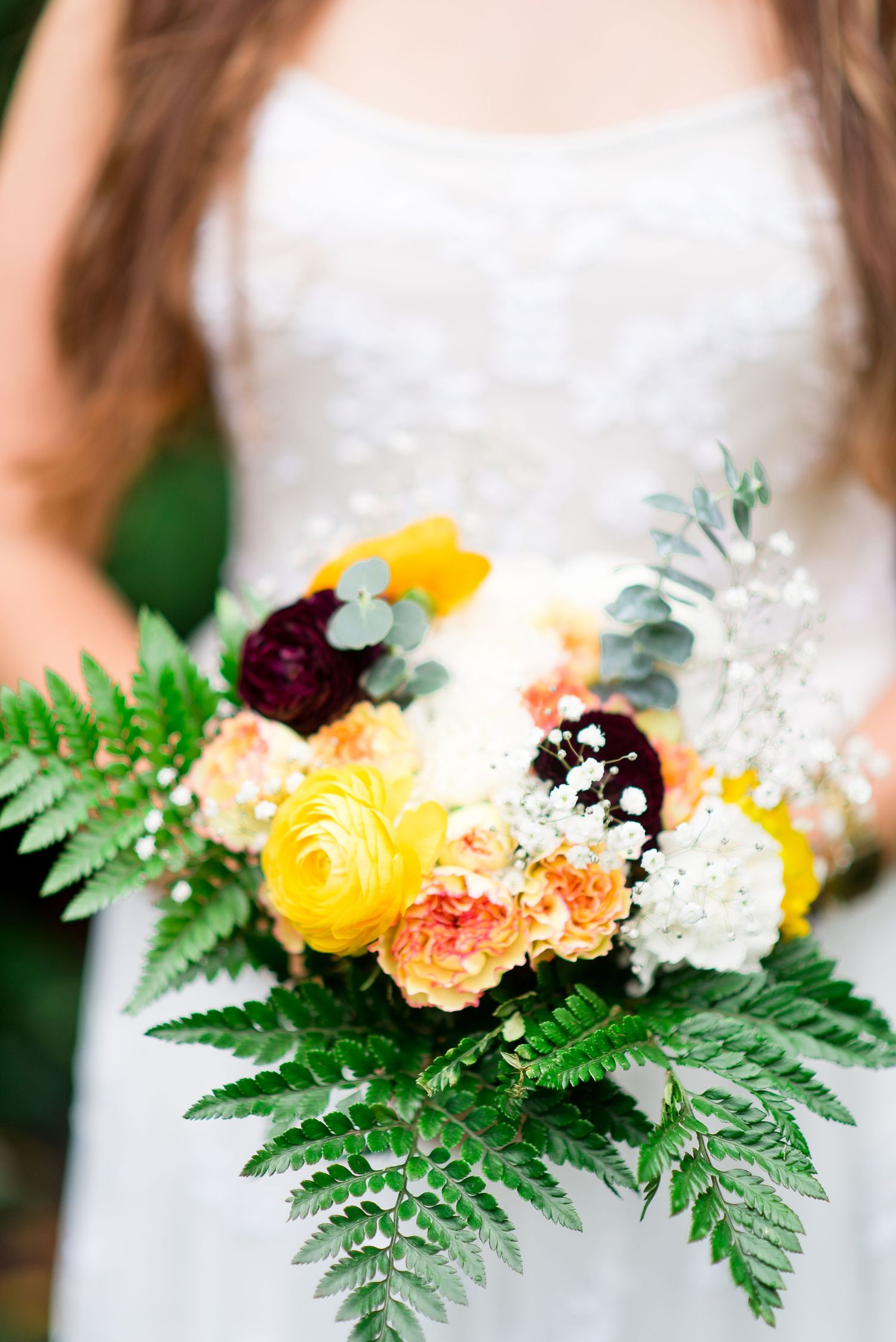 bride holding fall wedding bouquet with yellow and maroon flowers at Woman's Club of Evanston wedding