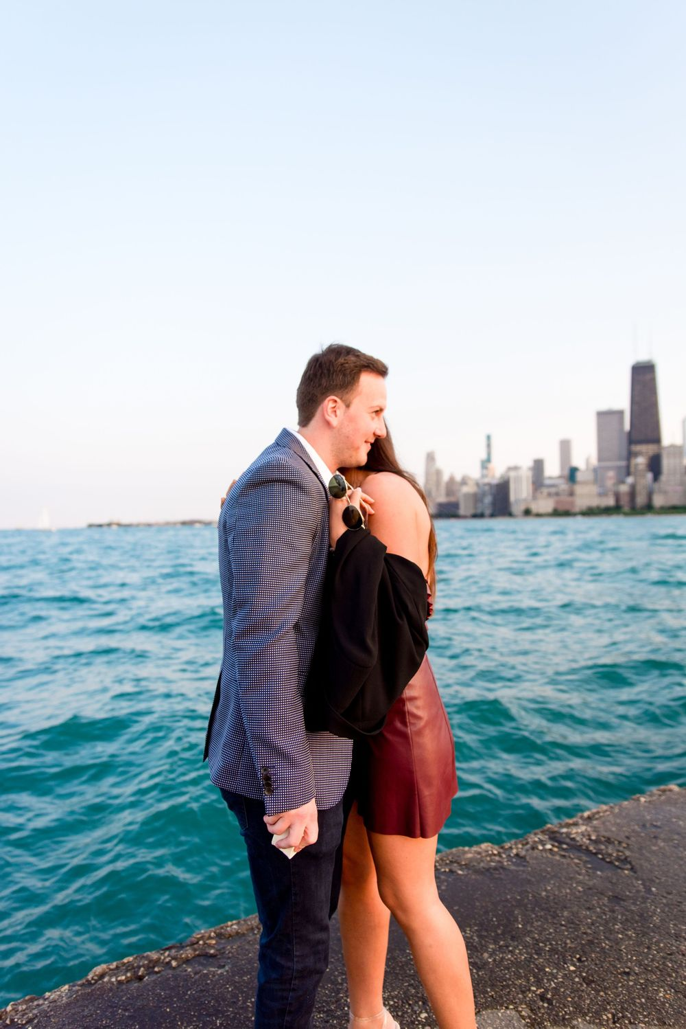 man and woman hugging after Chicago proposal at North Avenue Beach pier