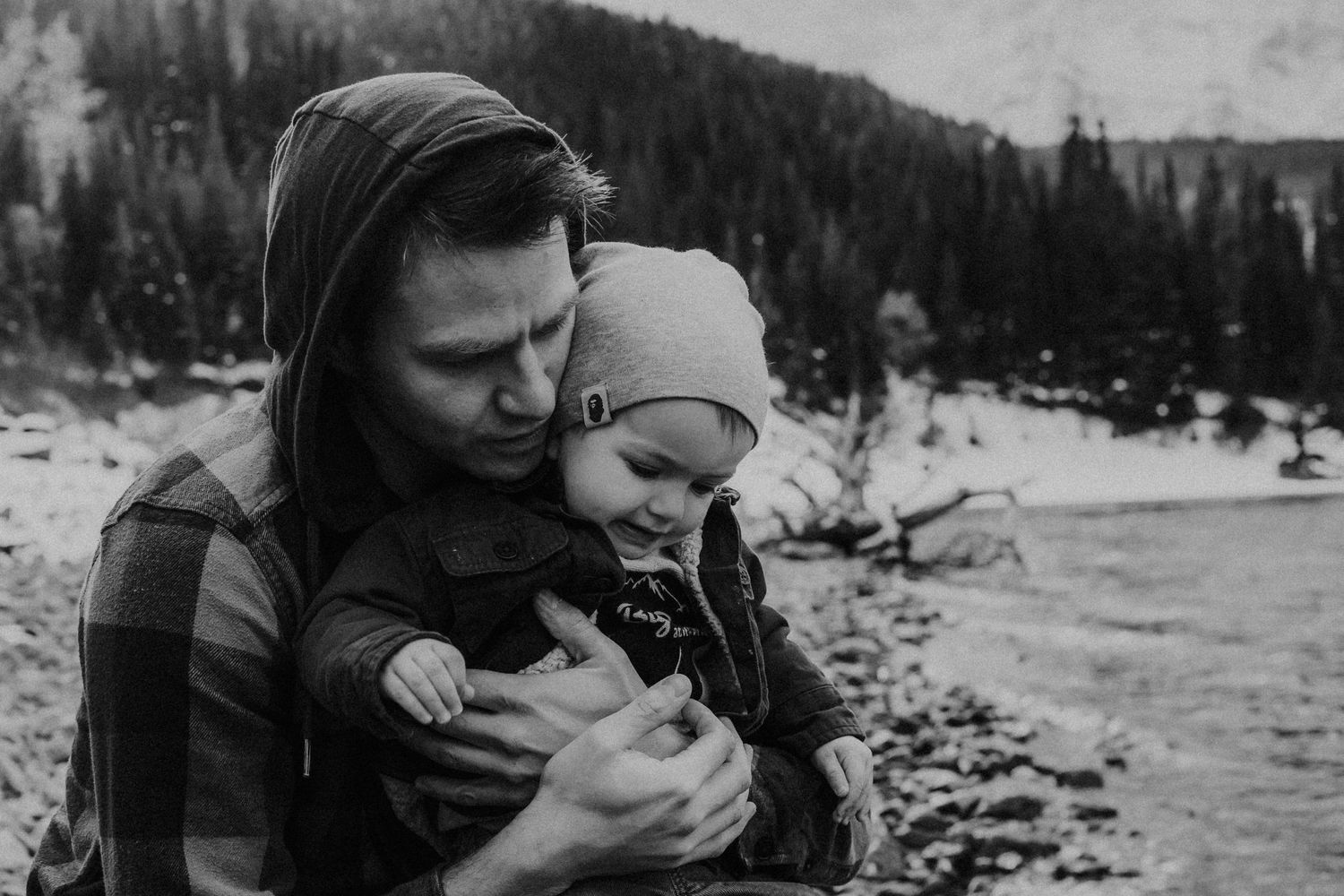 black and white photo of dad holding son on lake shoreline