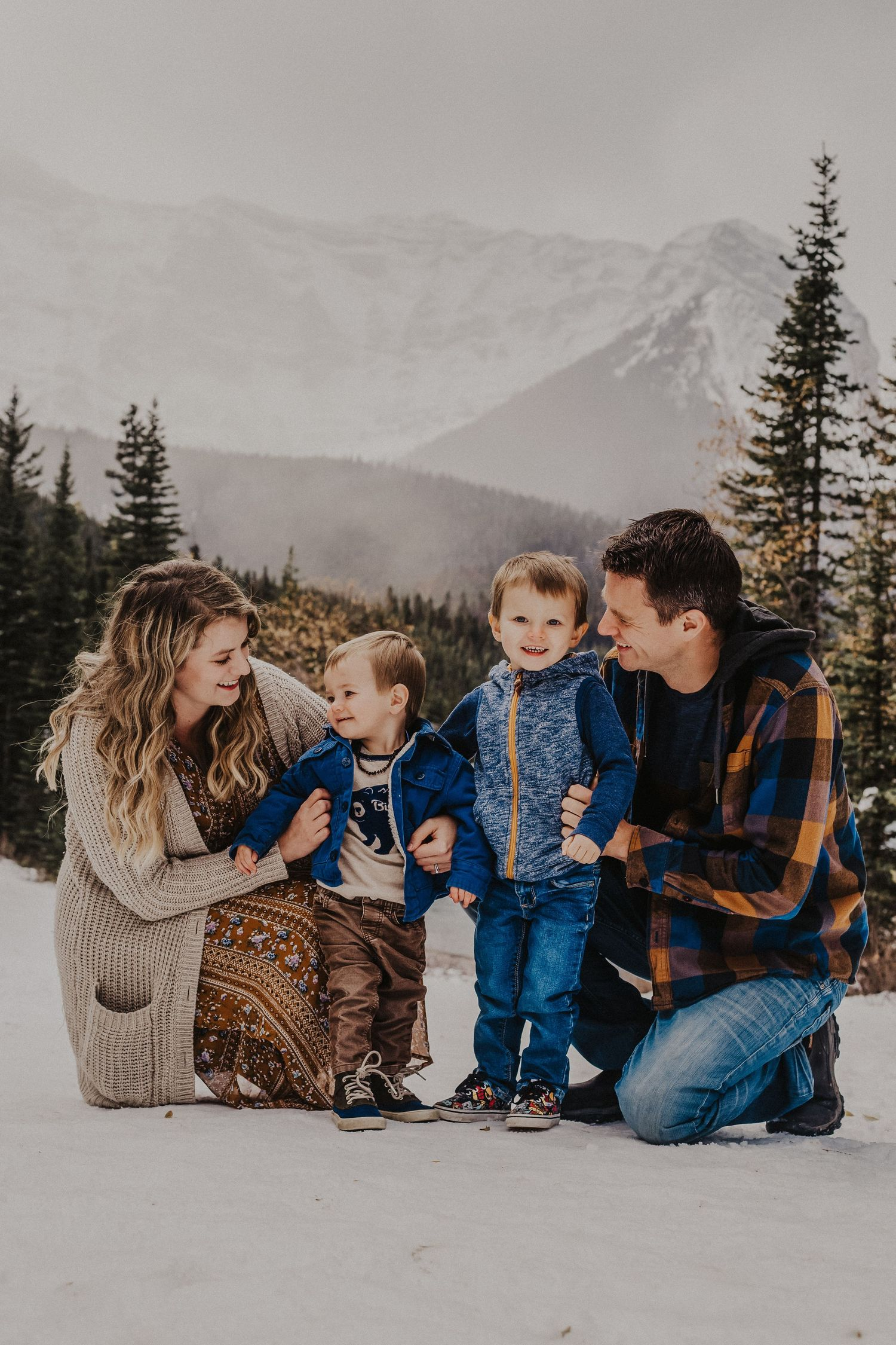 family cuddles and laughs in front of mountains