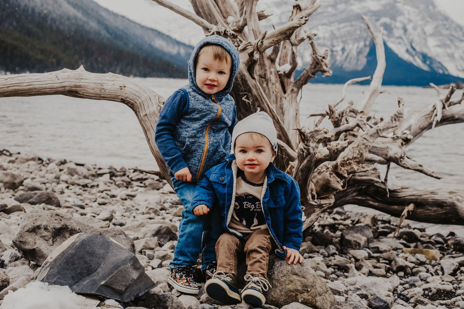 two boys in front of driftwood at mountain lake