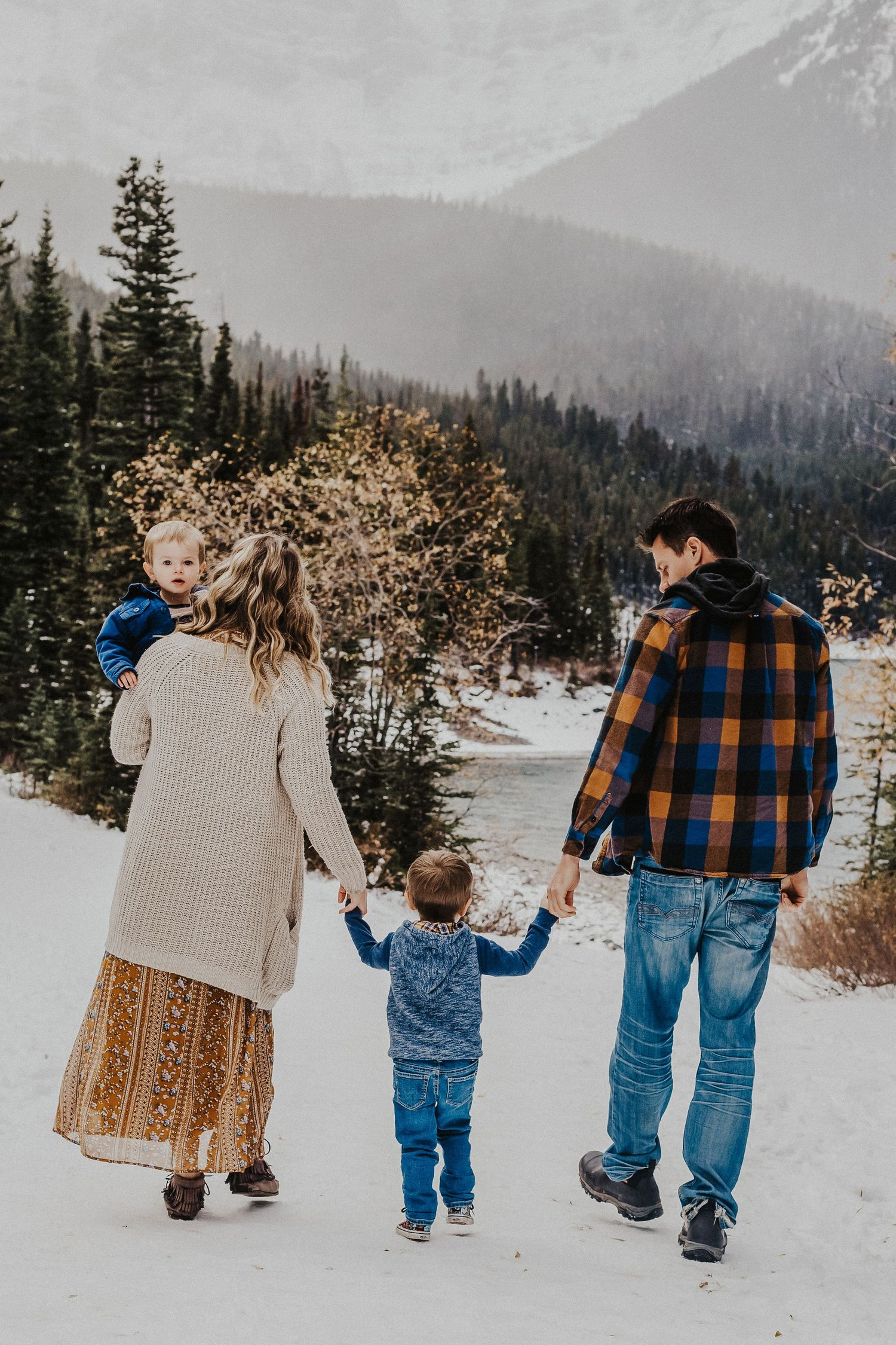 family of four walks hand in hand in front of mountains