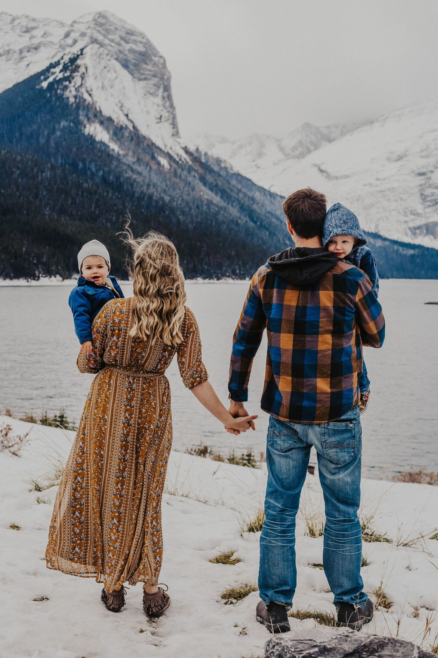 family stands and faces mountains while holding hands
