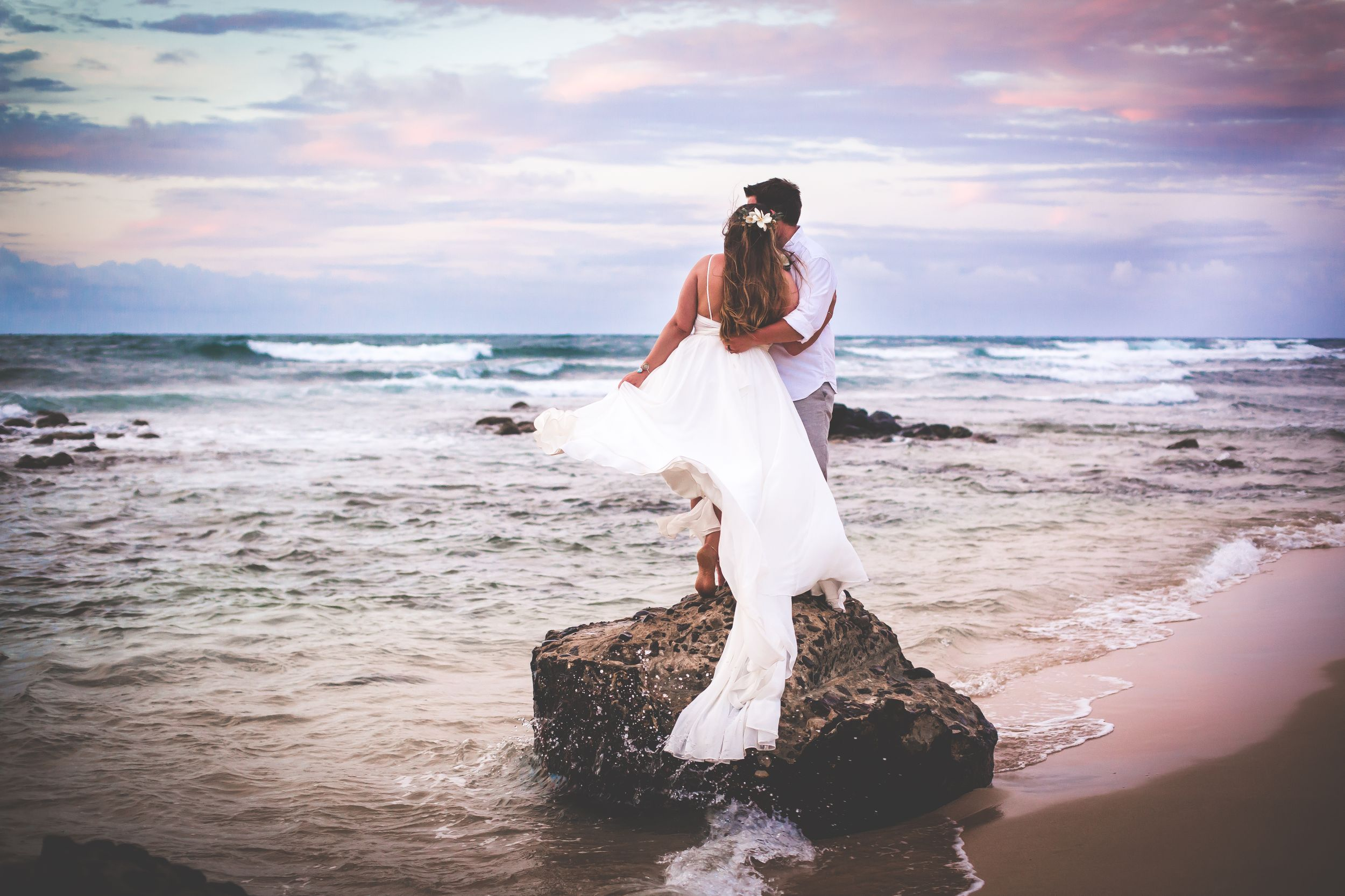 Bride and groom standing on a large rock in the ocean with a pastel sunset. They are embracing and looking at the water.