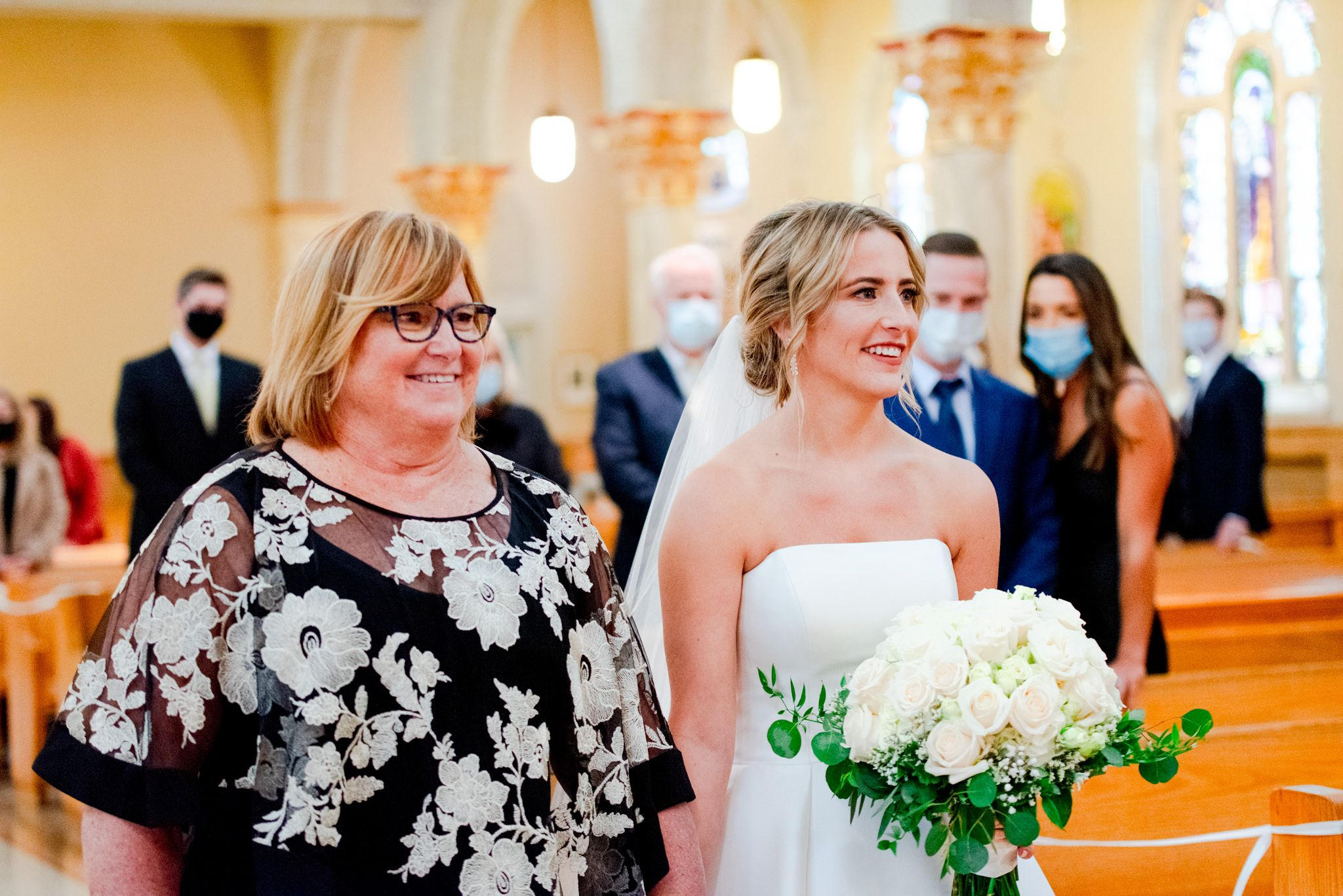 bride holding white bouquet and mother in glasses smiling as they walk down the aisle