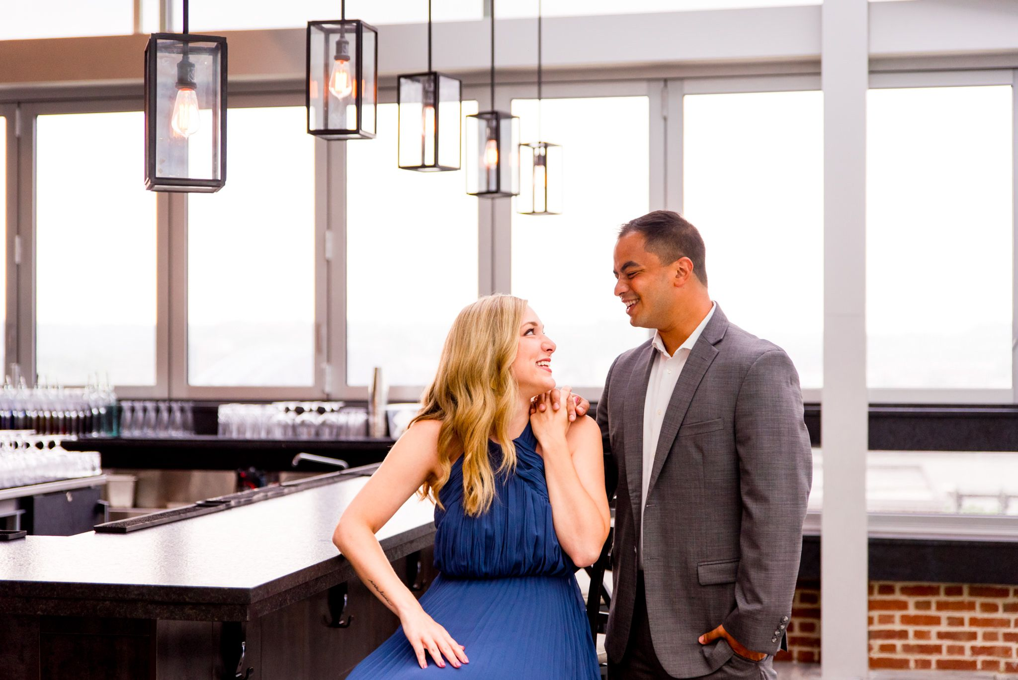 Asian man and blonde white woman hold hands and smile at each other at Vista, rooftop bar at Lytle Park Hotel