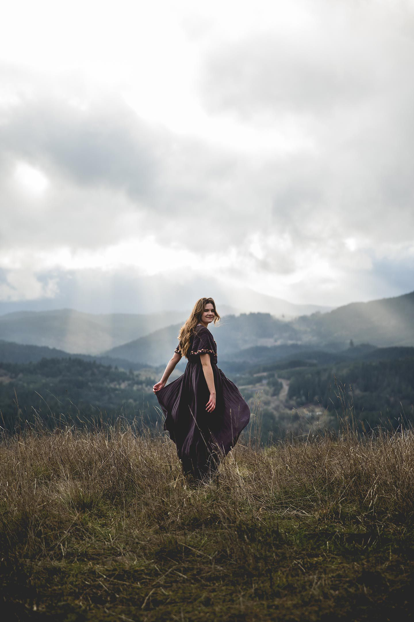 senior girl smiling and walking on a hill with the mountain and sun peaking through the clouds in the background.