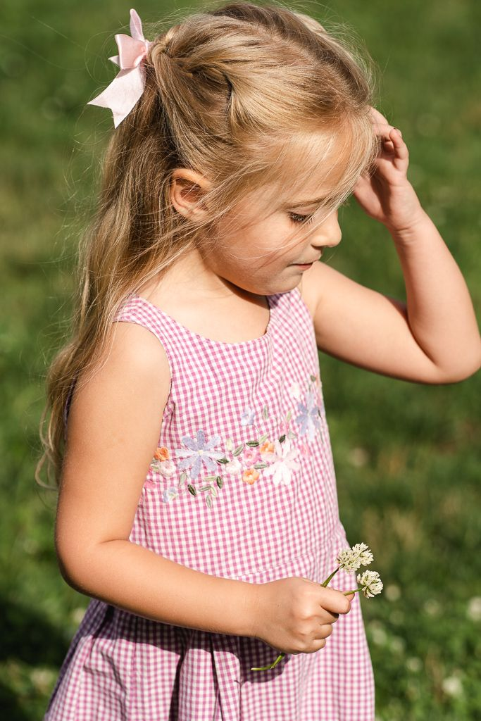 Candid photo of little girl holding flowers