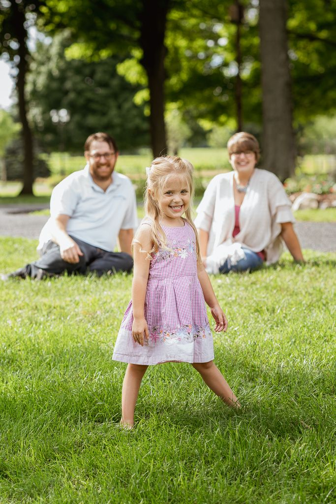 Young girl standing and smiling with parents sitting in background