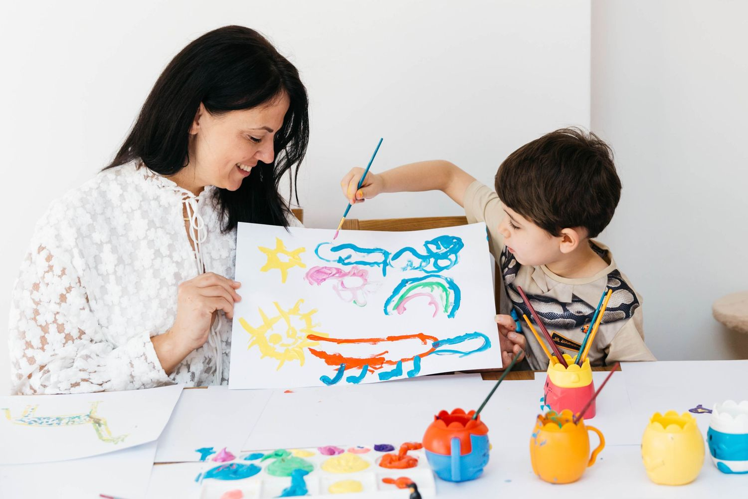 little boy showing off his colourful painting to mum