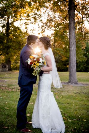 bride and groom kissing sunset