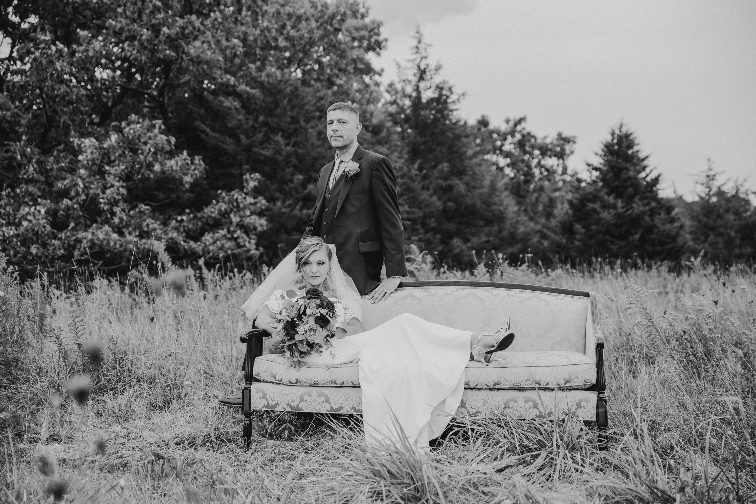 black and white bride and groom on a couch in a field