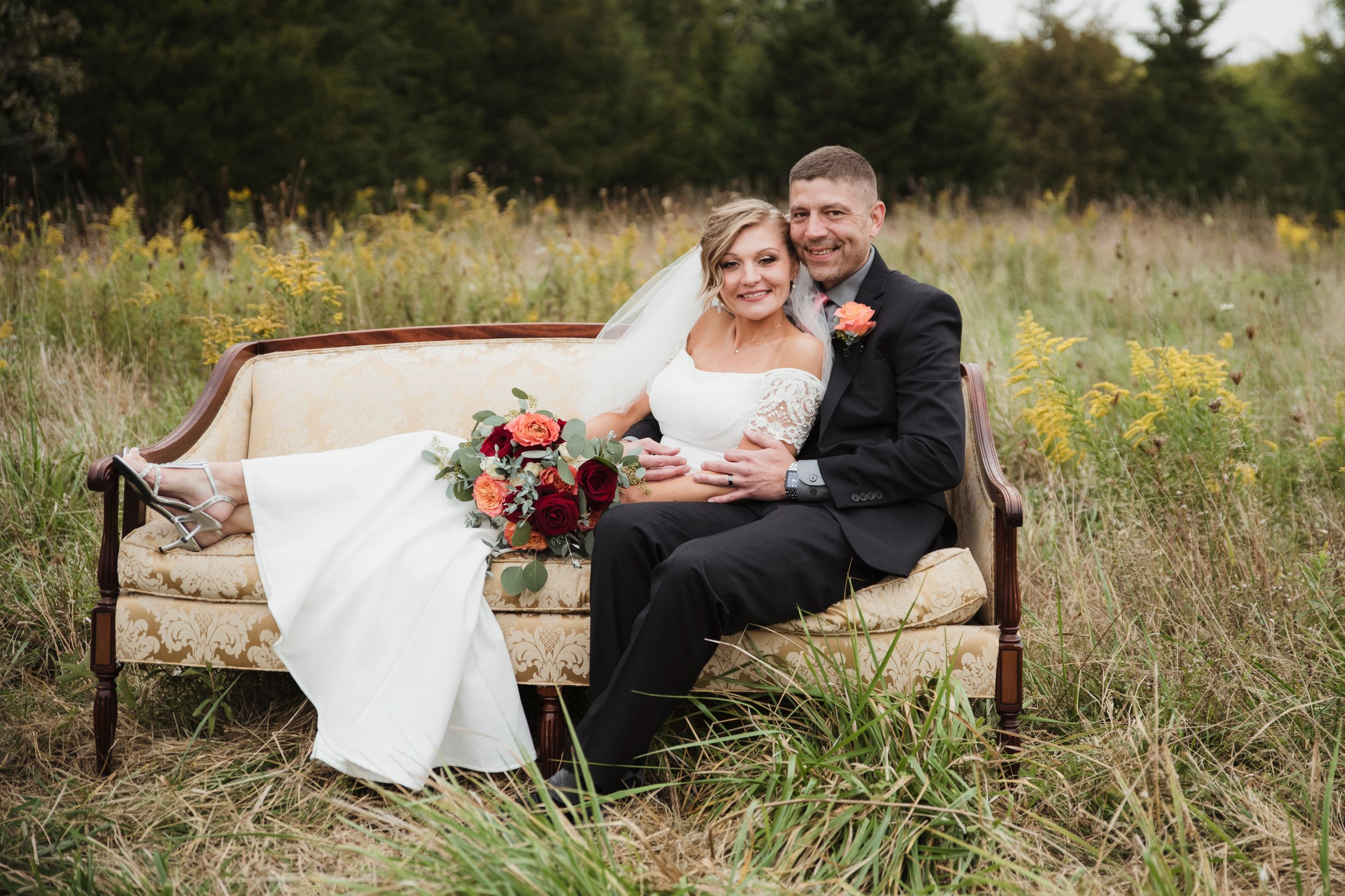 bride and groom on a couch in a field