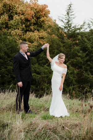 groom spinning bride in a field