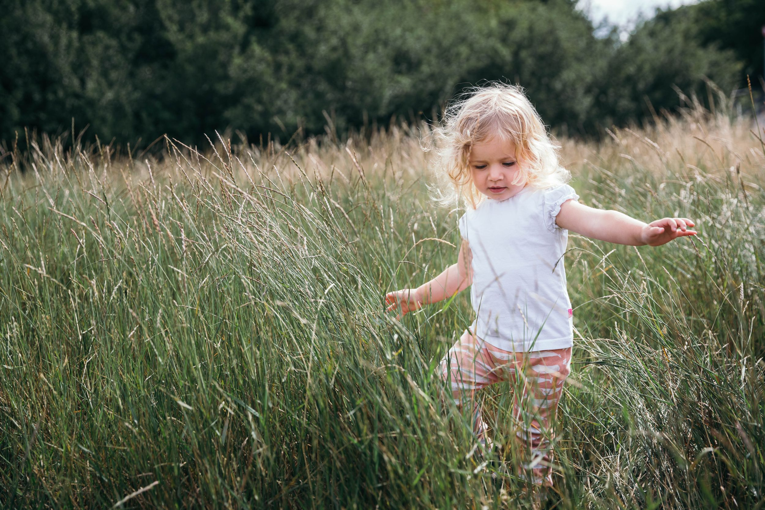 little blonde girl running through grass