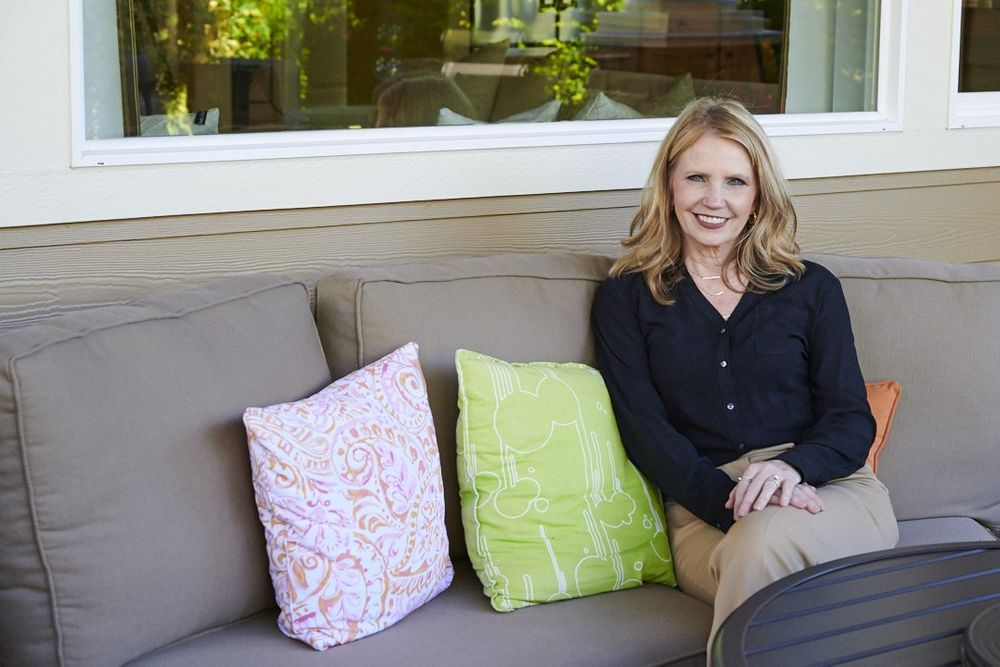 female real estate agent lounging on couch outside on patio