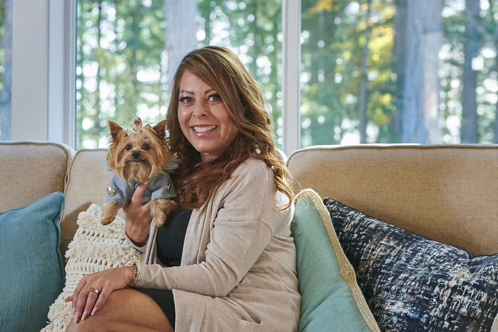 real estate agent sitting on couch holding pet dog
