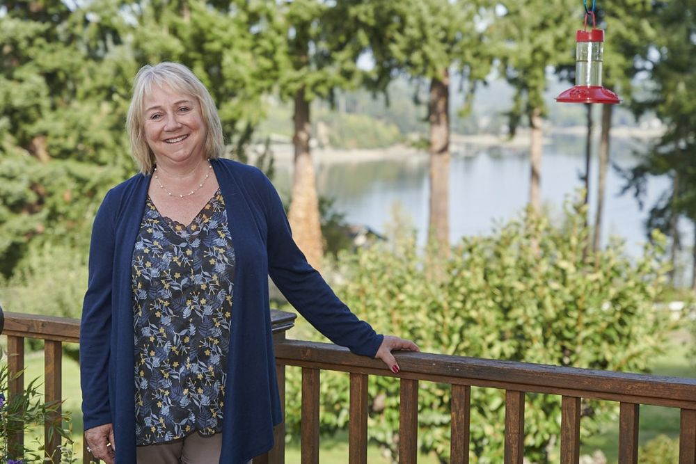 real estate agent standing with hand on deck railing at home