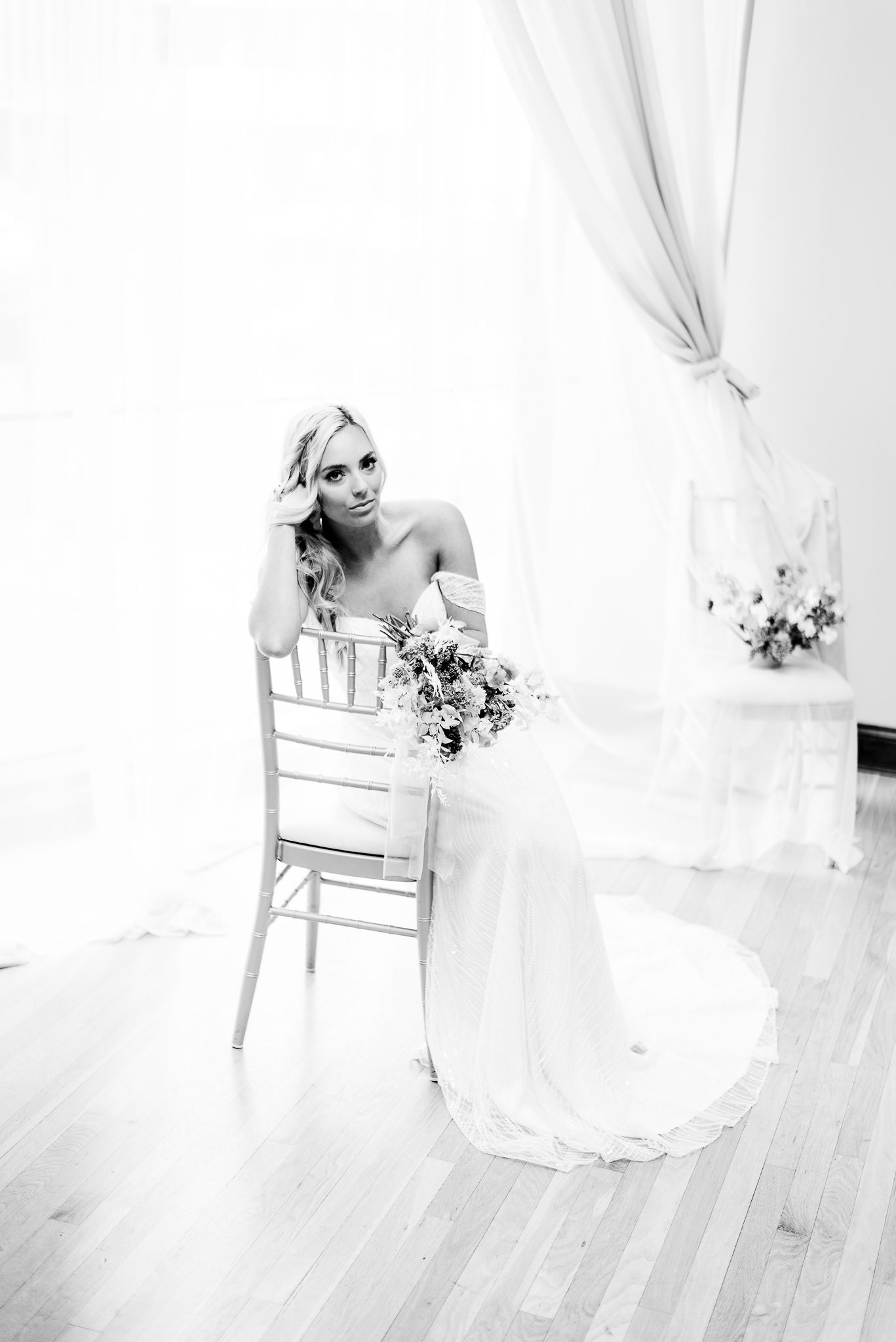 bride sitting in chair with bouquet looking at camera