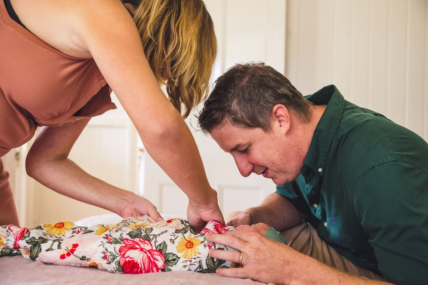 Mum wrapping baby with dad watching on