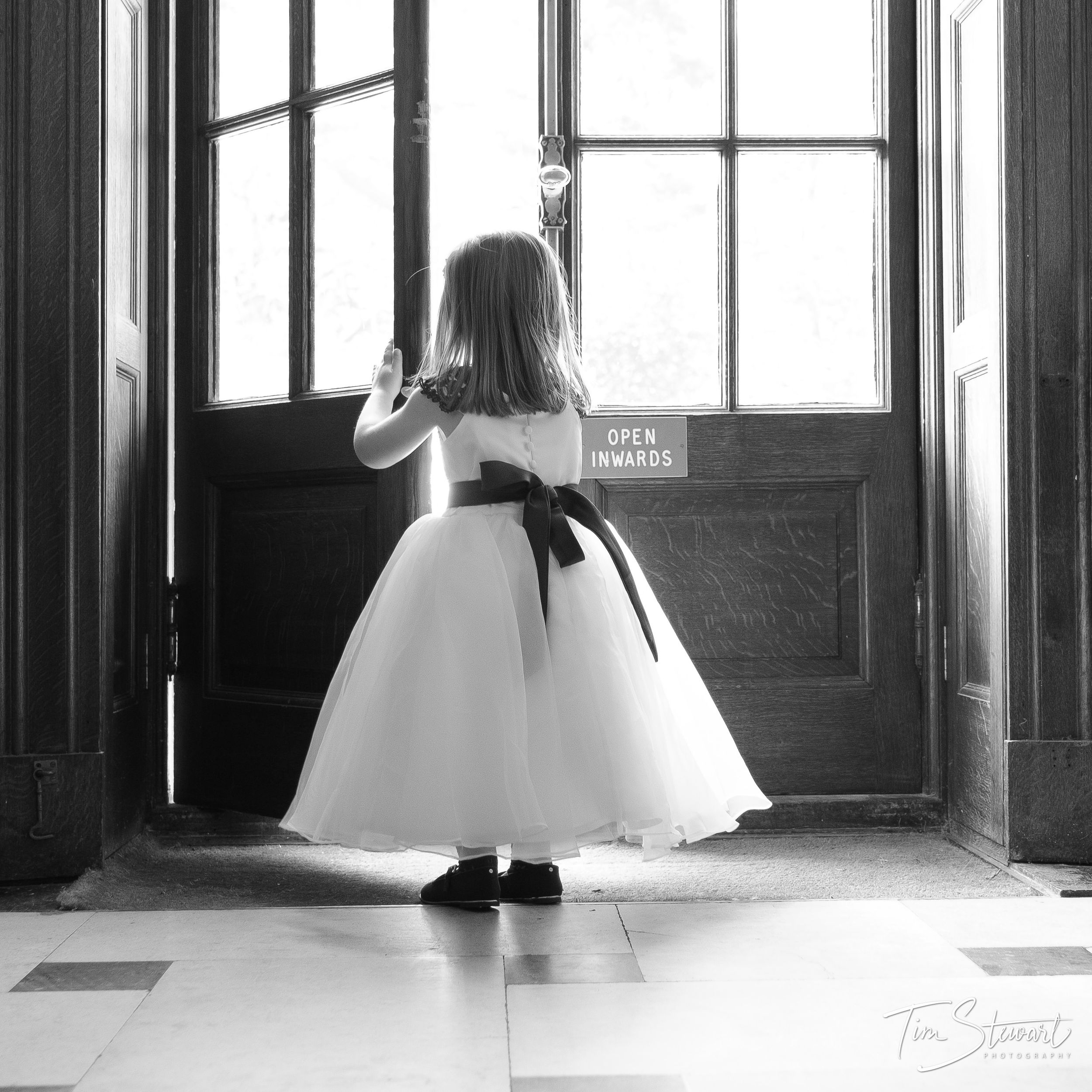 Little flower girl opening a big door at Crathorne Hall, Yarm. In black and white.