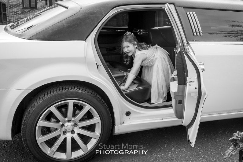 the flower girl smiles as she climbs into the limousine