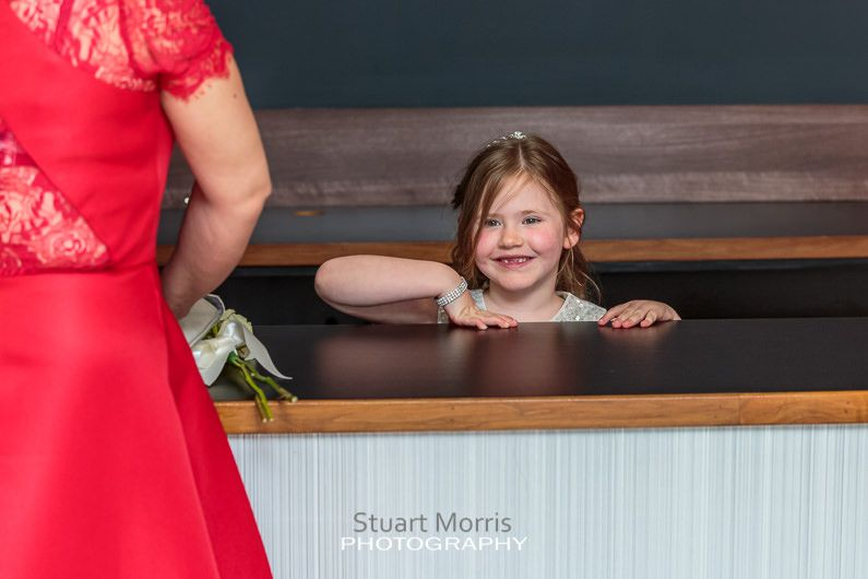 the flower girls smiles as she just about peeps from behind the reception desk at the bliss hotel southport