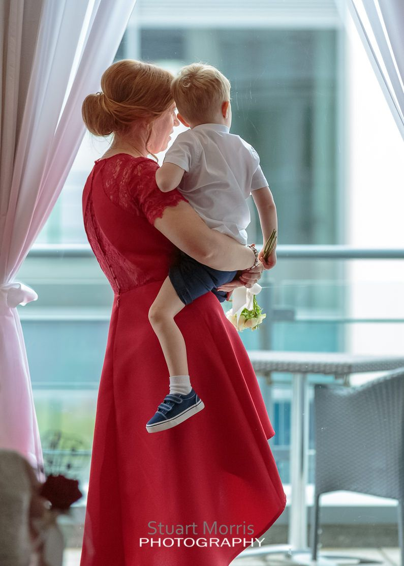 bridesmaid picks up her son and they look out of the window at the bliss hotel southport