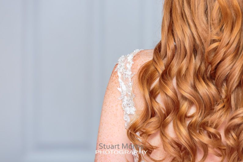 shot from behind of the brides wavy ginger hair and strap on her dress