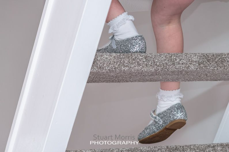 the flower girls litter silver shoes as the walks down the open staircase at the brides house