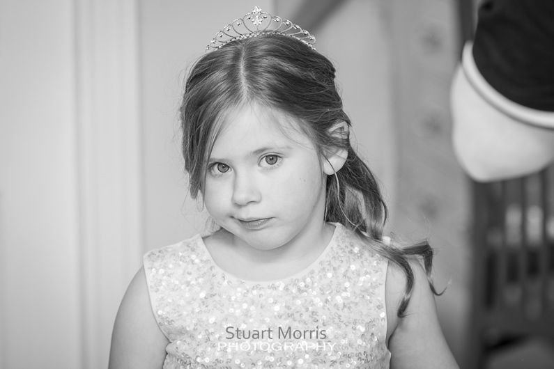 the flower girl looking bored as she stands getting her hair brushed